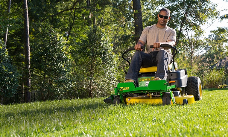 Man mowing grass with a Z235 with trees in the background.