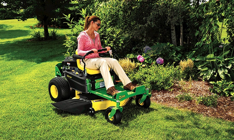Woman mowing grass around the edge of a flower bed with a Z255 zero-turn mower.