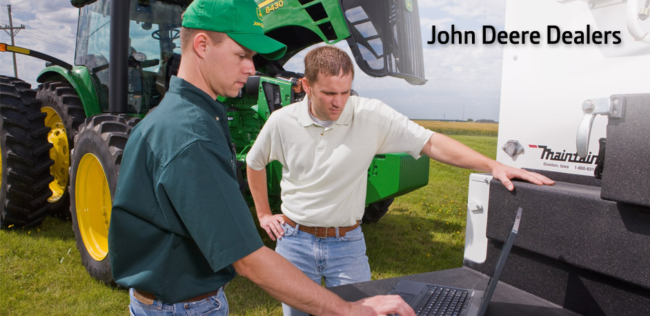 John Deere Dealer and farmer looking at a laptop with a John Deere tractor in the background