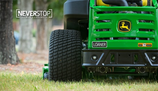 Closeup of the font of a John Deere mower with a Loaner sticker attached