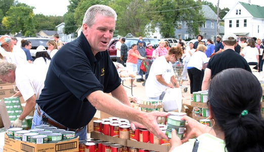Man with John Deere shirt hands out canned goods