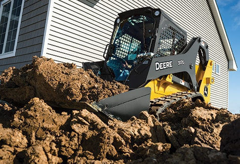 Ground level view of a 317G Compact Track Loader moving dirt at a home construction site