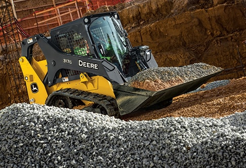 Right hand view of a 317G Compact Track Loader transporting gravel at a construction site
