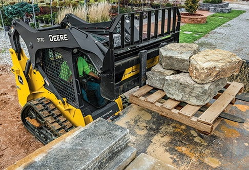 Right hand view of a 317G Compact Track Loader with a rail style pallet fork attachment loading landscaping stones onto a truck