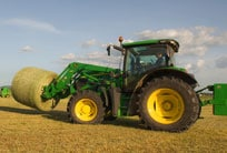 6R Series tractor with hay bale on loader attachment