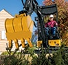 Front view of the 17G compact excavator digging up a sidewalk