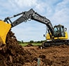 Rear three quarter view of 180G LC Excavator digging dirt