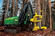 Closeup of a 903M Tracked Feller Buncher sawing into a group of trees at a job site