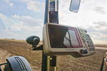 GreenStar 2 1800 Display in a tractor cab overlooking a tilled field