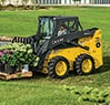 Left hand view of a 312GR Skid Steer with rail style pallet fork attachment transporting large flowerpots