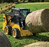 Rear three quarter view of 316GR Skid Steer with AF66 ag fork attachment moving a round hay bale