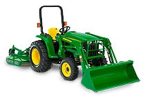 Man driving a 3038E Series Compact Utility Tractor with loader implement and box blad attachment in front of a house