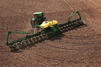 John Deere tractor with implement completing an end turn in a field