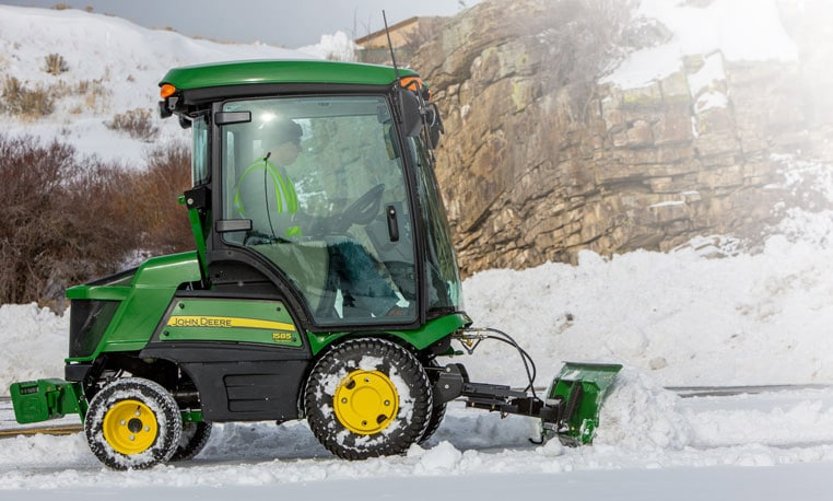 Front mower with blade attachment pushing snow