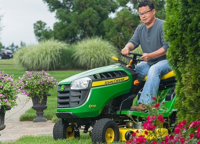 Man using D110 lawn tractor to edge flower bed along lawn.