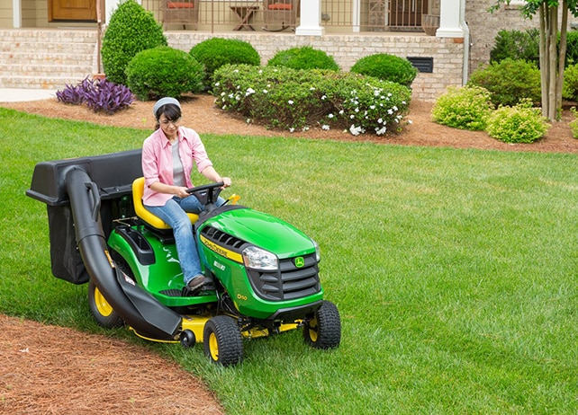 Woman driving D110 lawn tractor with bagger