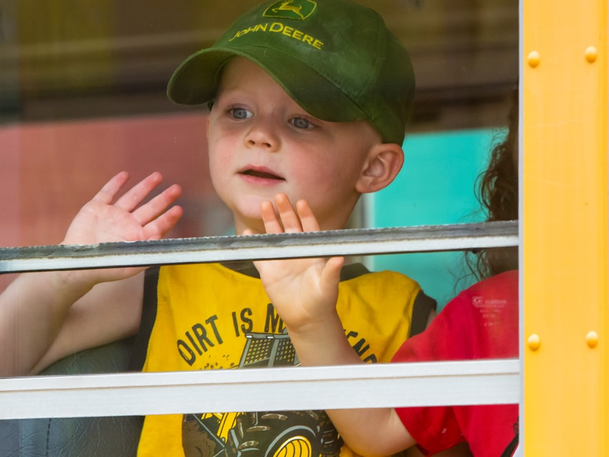 Boy on school bus in John Deere cap
