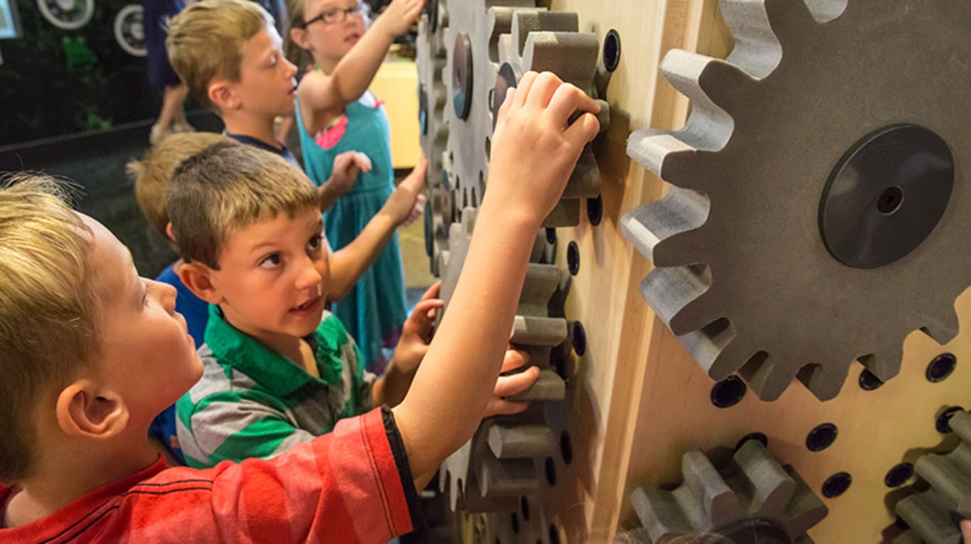 Children work to assemble an interactive gear display