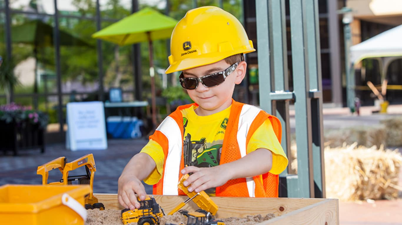 A boy wearing hard hat and safety vest plays with trucks in the sand