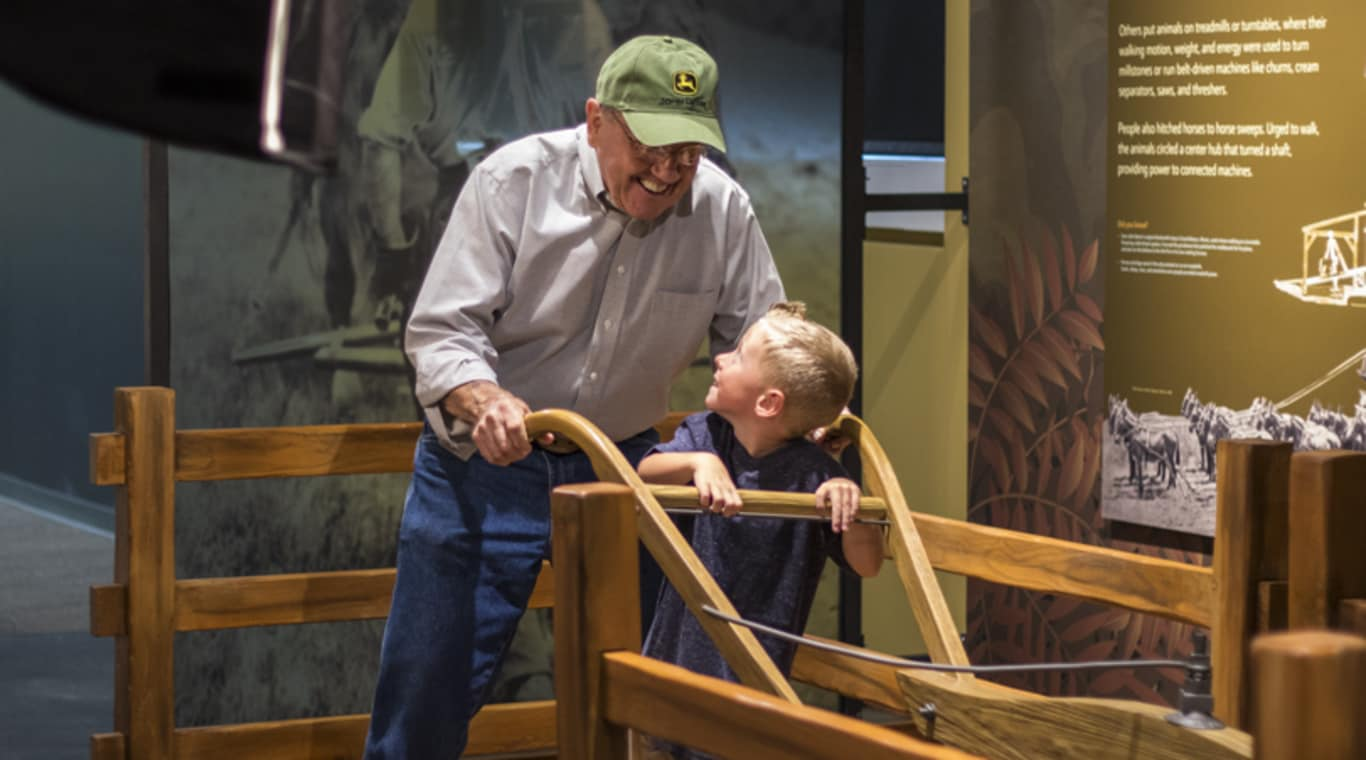 A man and his grandson stand behind a replica of the original John Deere plow