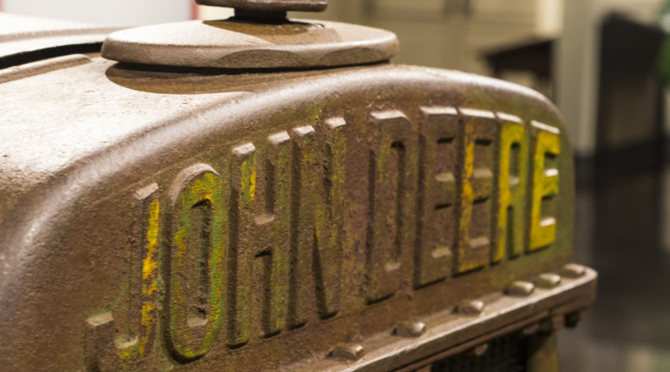"The front end of a tractor prominently displays the name ""John Deere"""