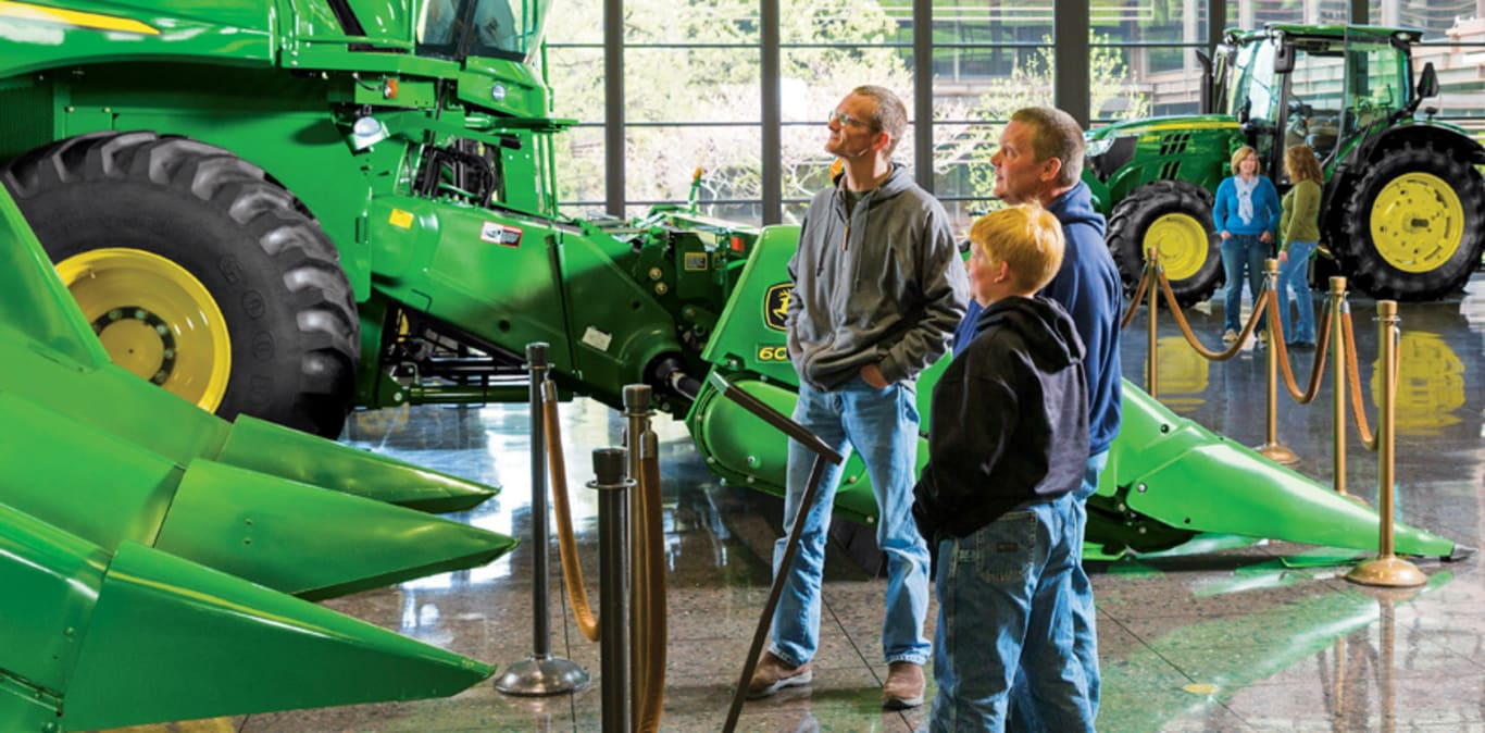Three people look up at a John Deere combine on the display floor