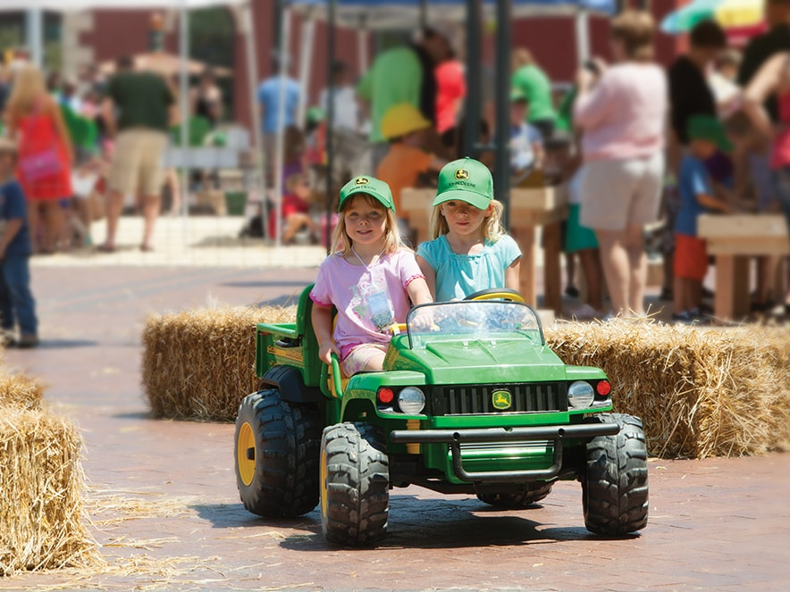 Two girls ride in a small toy John Deere Gator