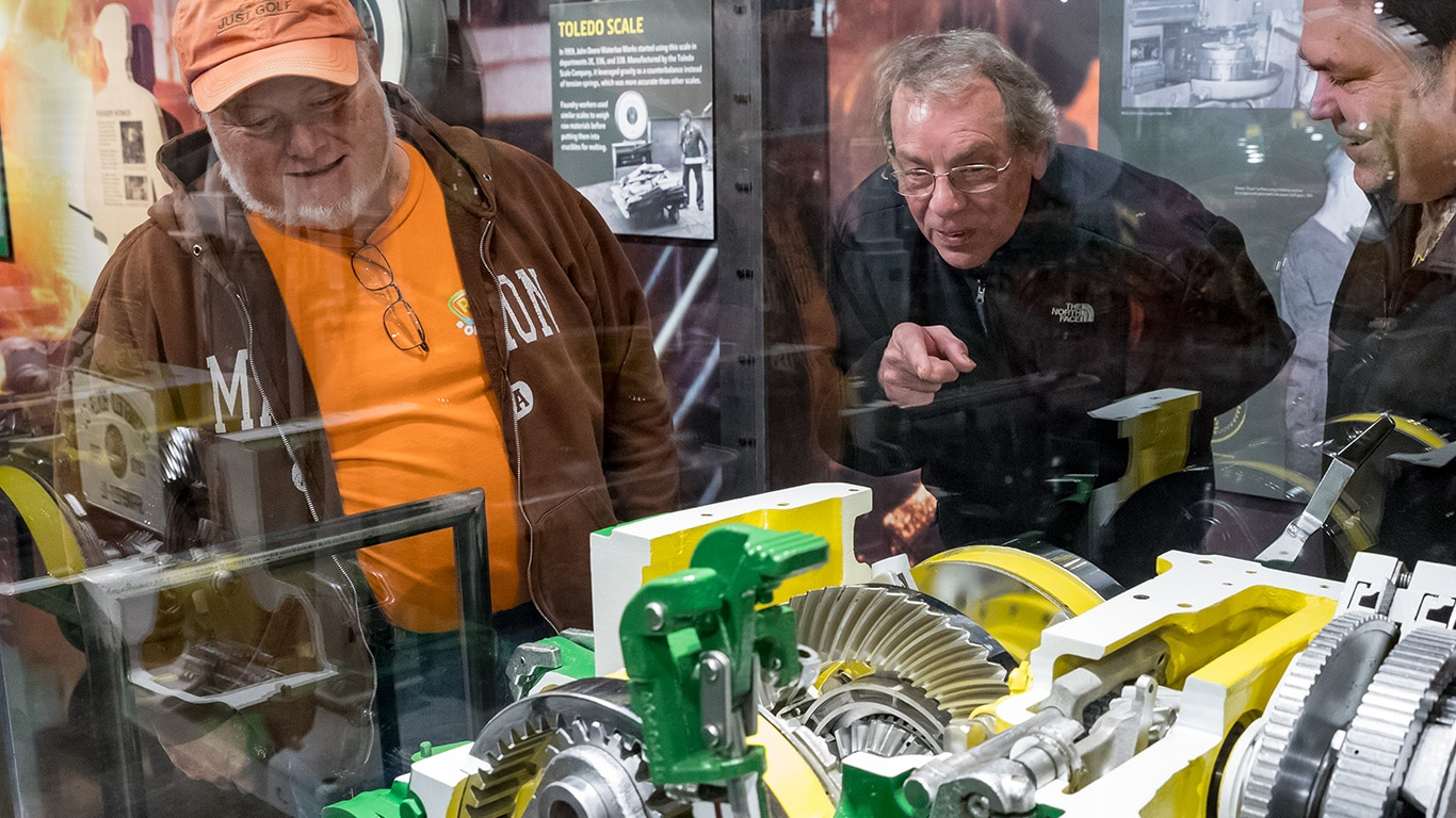 People examining a tractor cutaway on display at the John Deere Tractor and Engine Museum