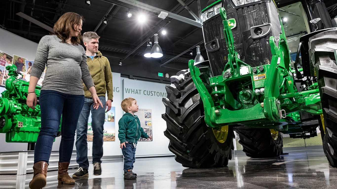 A boy walking around a large tractor with mom and dad