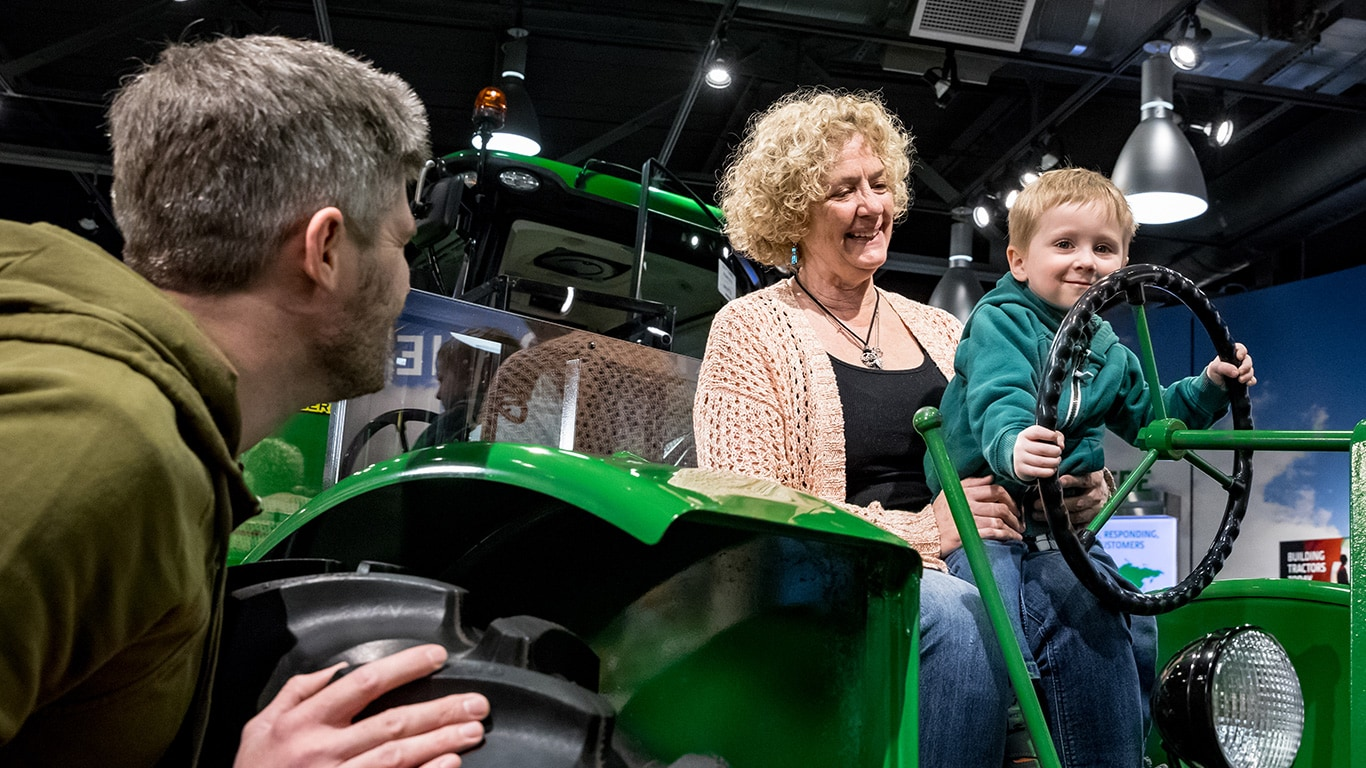 Father looking on as boy sits on grandma's lap on a vintage tractor