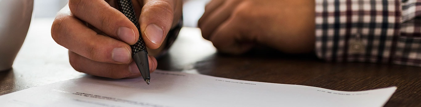 Image of someone signing a document