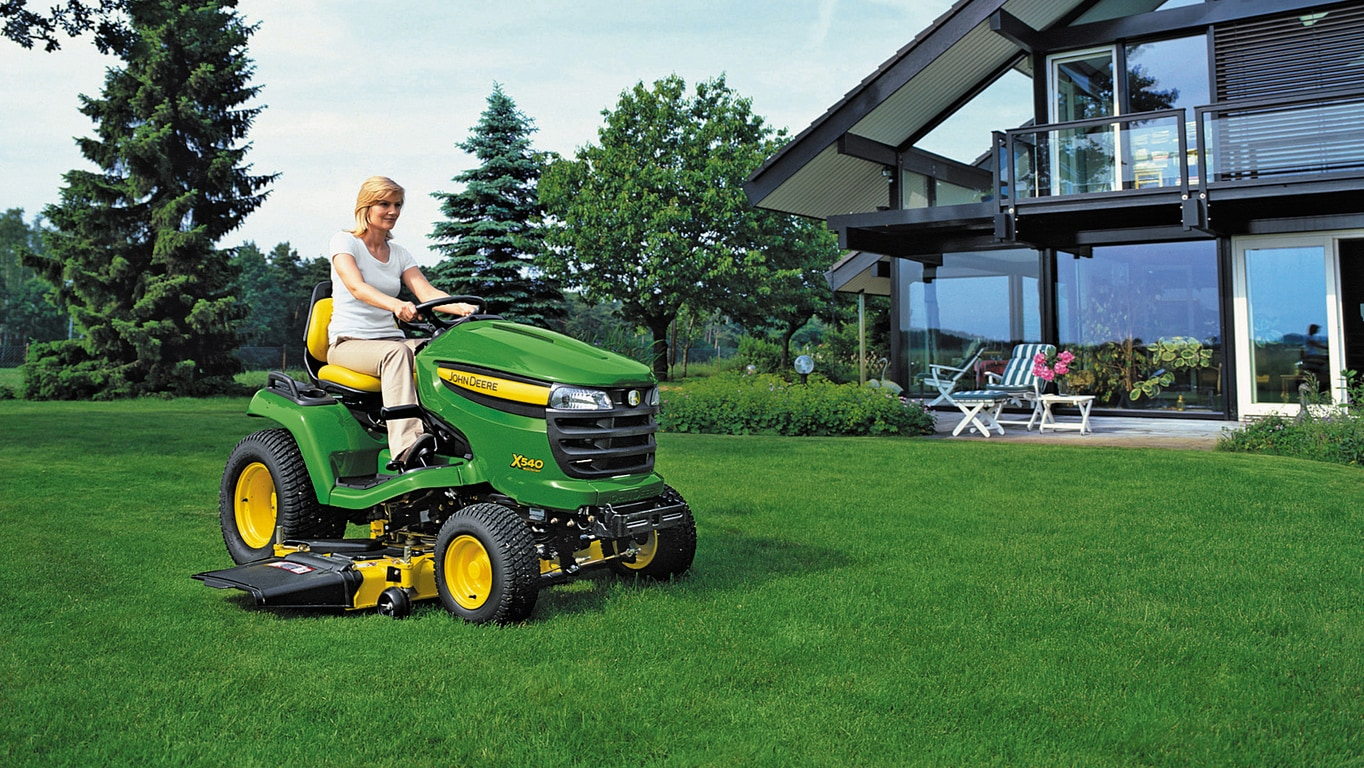 Woman mowing with a John Deere x540 Lawn Tractor