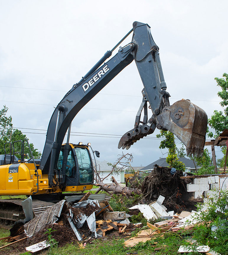 210G Excavator drops a load of rubble from its bucket with claw while cleaning up around a building severely damaged from a hurricane