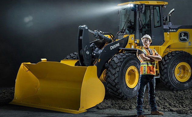 An operator stands proud with arms crossed in front of a 644L Wheel Loader parked on a pile of dirt