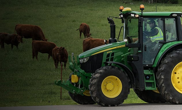 Man driving a 6M tractor along side a cow pasture.