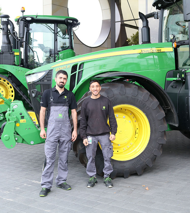 Two male refugees stand in front of John Deere 8 series tractor