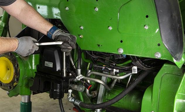 Person installing AutoTrac™ Controller 300 on a tractor
