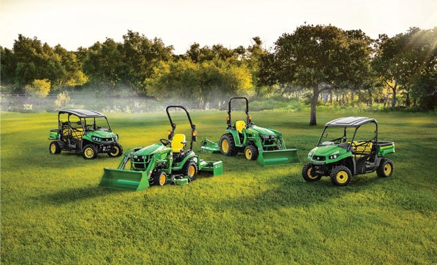 Four John Deere products in a green field with trees and fog in background.