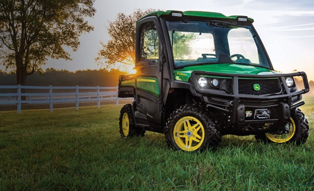 An XUV835R sitting inside a fenced-in pasture with the morning sun coming up in the background.