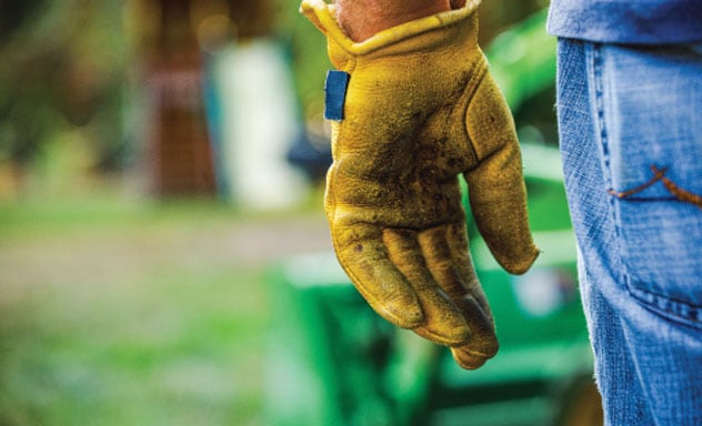 close up of a person's work glove and jeans