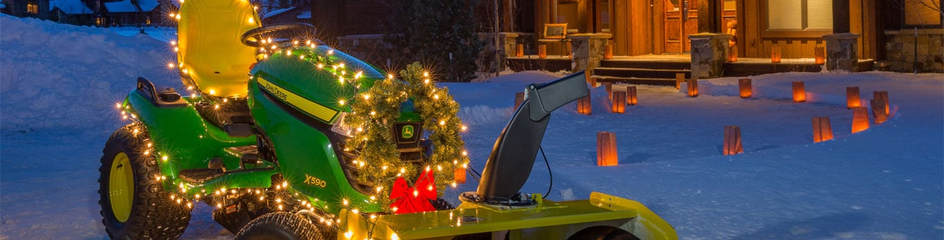 Z590 lawn tractor decorated with lights and wreath with snow thrower attachment in front of house.