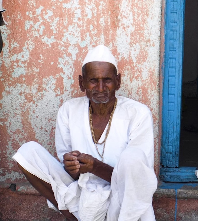 Indian man sits against the exterior wall of a home.