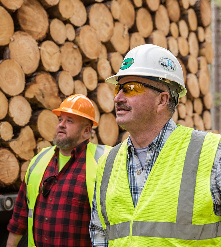 Paul Burton and Tuffy Burton inspect the large pile of logs stacked on their trailer