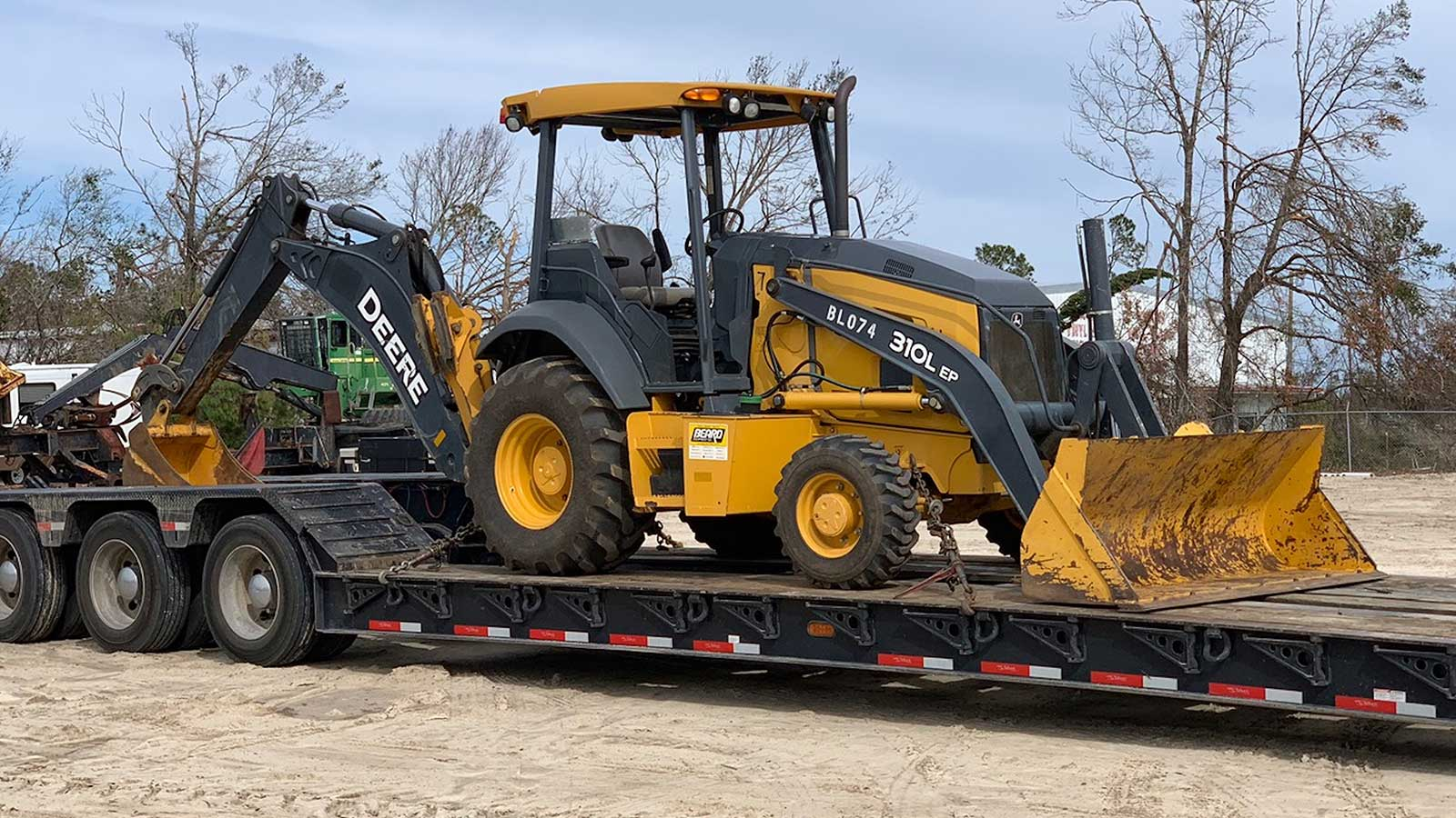 310L backhoe on a trailer ready to be delivered to the impacted area