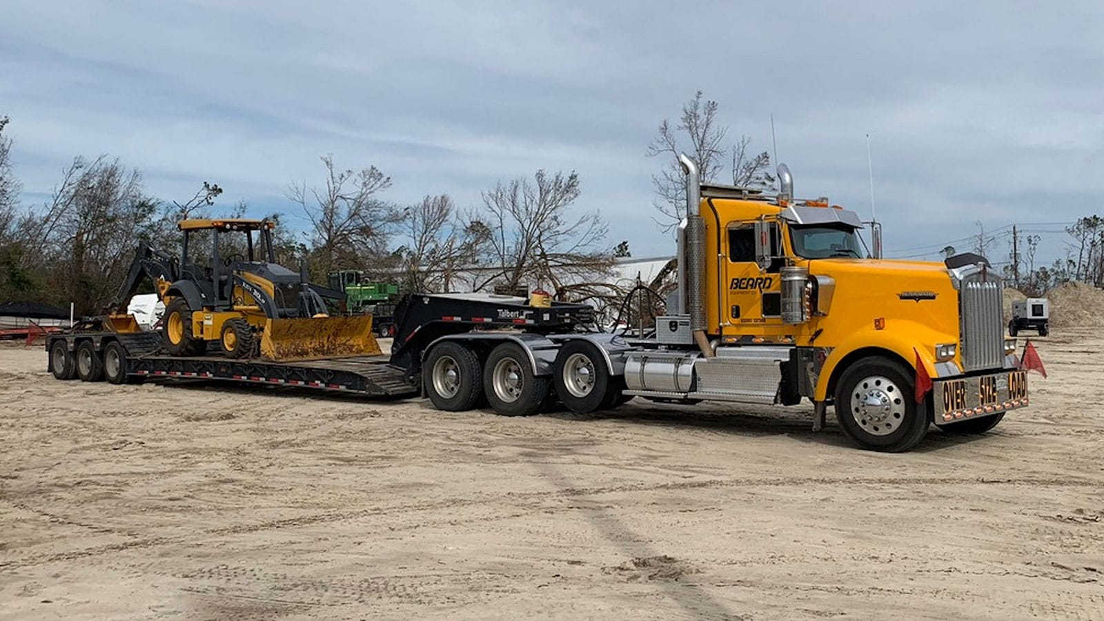 L-Series backhoe on a trailer behind a truck for delivery to the impacted area