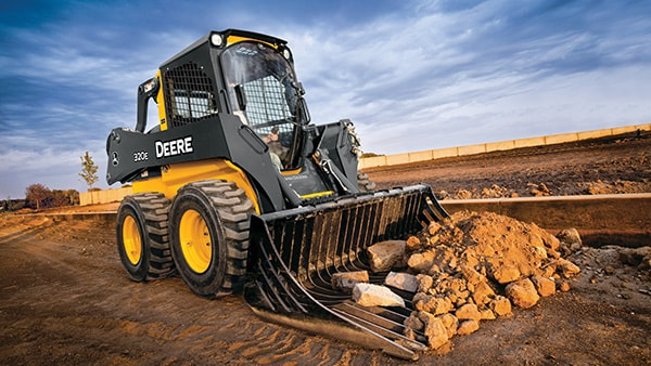 320E Skid Steer with Rock Bucket attachment scooping up rocks and dirt on a jobsite