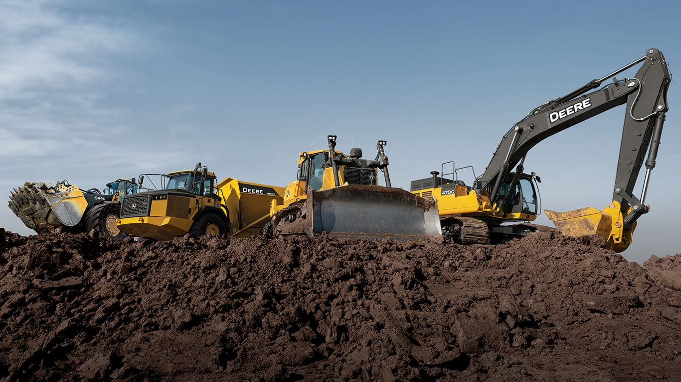 large dozer climbs a dirt pile while a large excavator loads a dump truck