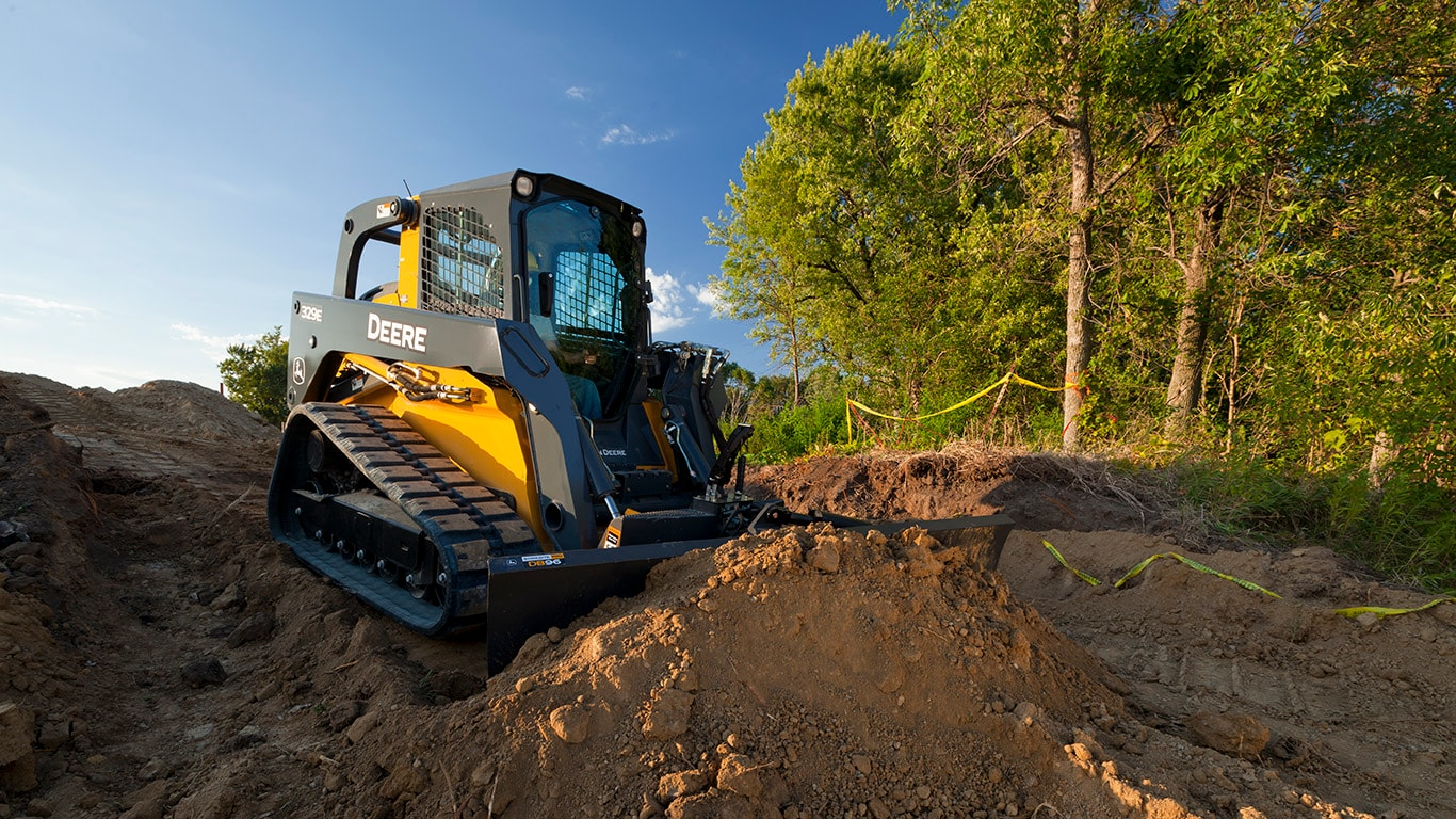 323E Compact Track Loader with Dozer Blade attachment pushing dirt on a job site.