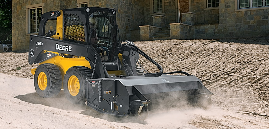 326D Skid Steer with Pick up broom attachment sweeping at a residential construction jobsite.