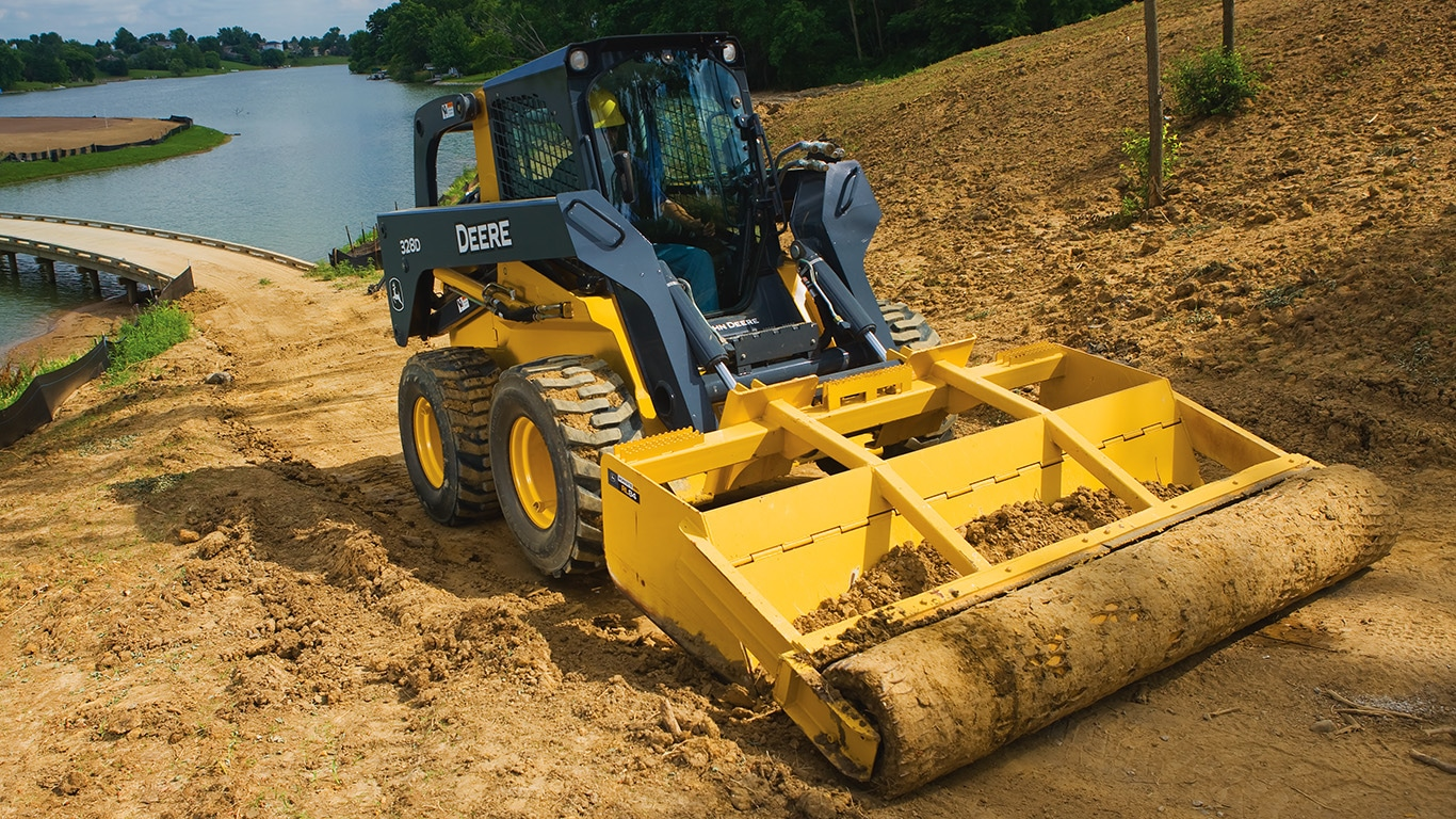 Skid Steer with roller level attachment compacting dirt near a lake.